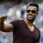 "FILE - In this July 1, 2014 file photo, singer Romeo Santos, known as the ""King of Bachata,"" waves to fans during a pre-game ceremony before a baseball game at Yankee Stadium in New York. Santos is nominated in 10 categories for next year's Premio Lo Nuestro music awards to be held Feb. 19, 2015. (AP Photo/Kathy Willens, File)"